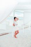 Frau, Brunette mit dem kurzen Haar im weißen Kleid auf dem Strand von Ozean, Meer nahe Sonnenblende, Zelt ferien Stockbild