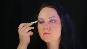 Frau Brunette mit purpurrotem Schatten des Augenmakes-up stock footage