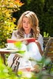 Frau am Buch-Messwert im Garten Stockfotografie