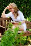 Frau am Buch-Messwert im Garten Lizenzfreie Stockfotografie