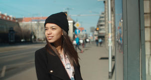 Frau am Bushaltestelle-Lesezeitplan Stockfotos