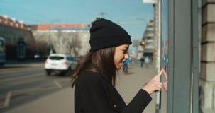 Frau am Bushaltestelle-Lesezeitplan Lizenzfreies Stockbild