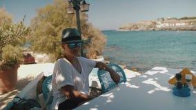 Frau in Caféwarteauftrag Nettes junges Mädchen im Hut und in der Sonnenbrille im Café, das weg beim Sitzen auf Tabelle schaut stock video