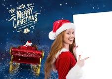 Frau 3D in Sankt-Kostüm zeigend auf Plakat mit Weihnachtsmann-Reitrenpferdeschlitten in Richtung zur SK Lizenzfreie Stockbilder