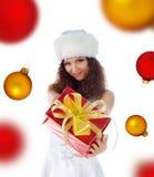 Frau das Weihnachtsgeschenk auf einem Kugelhintergrund Lizenzfreies Stockbild
