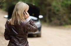 Frau an defektem Auto mit Handy Stockbild