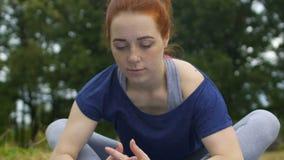 Frau dehnt Beine in der Schmetterlingsposition aus, die vorwärts, Jogi in Park asana verbiegt stock footage