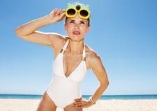 Frau in den Ananasgläsern, die in den Abstand Strand betrachten Stockfoto