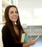 Frau in den Bibliotheksbestandbüchern und -telefon Stockfoto
