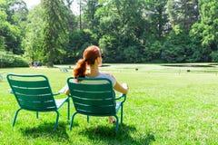 Frau in den Brillen entspannen sich auf Greenfield lizenzfreies stockbild