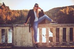 Frau in den Denimjeans und -Sonnenbrille, die auf einer Brücke sitzen Stockfotos