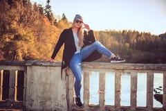 Frau in den Denimjeans und -Sonnenbrille, die auf einer Brücke sitzen Lizenzfreies Stockbild