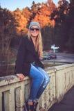 Frau in den Denimjeans und -Sonnenbrille, die auf einer Brücke sitzen Stockfoto