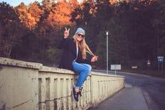 Frau in den Denimjeans und -Sonnenbrille, die auf einer Brücke sitzen Lizenzfreie Stockfotos