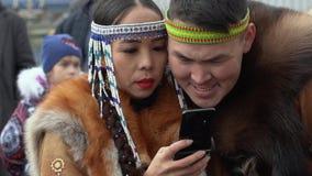 Frau in den einheimischen Einwohnern der nationalen Kleidungs liest Mitteilungen im Smartphone stock video