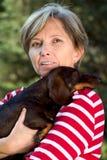 Frau in den Fünfziger Jahren, die einen Hund anhalten lizenzfreie stockfotos