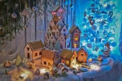 Frau in den Feiertagsvorbereitungen, welche die Verglasung auf Lebkuchenhaus Weihnachtsbäume setzen stockfotos