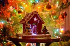 Frau in den Feiertagsvorbereitungen, welche die Verglasung auf Lebkuchenhaus Weihnachtsbäume setzen Stockfotografie