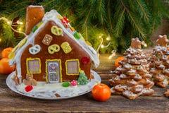 Frau in den Feiertagsvorbereitungen, welche die Verglasung auf Lebkuchenhaus Weihnachtsbäume setzen Lizenzfreie Stockfotos
