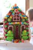 Frau in den Feiertagsvorbereitungen, welche die Verglasung auf Lebkuchenhaus Weihnachtsbäume setzen Stockfoto
