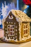 Frau in den Feiertagsvorbereitungen, welche die Verglasung auf Lebkuchenhaus Weihnachtsbäume setzen Lizenzfreies Stockfoto