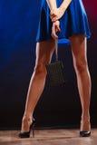 Frau in den Fersen hält Handtasche, Discoclub Stockfoto