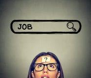 Frau in den Gläsern denkend, nach einem neuen Job suchend lokalisiert auf grauem Wandhintergrund Stockfoto