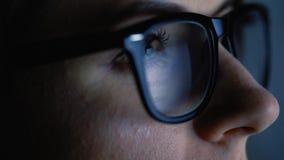Frau in den Gläsern, die auf dem Monitor und dem surfenden Internet schauen stock footage