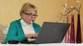 Frau in den Gläsern schreibt Text unter Verwendung des Laptops und des Rauchens einer Zigarette stock footage