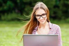 Frau in den Gläsern unter Verwendung des Laptops stockbild