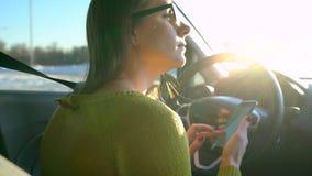 Frau in den Gläsern unter Verwendung eines Smartphone im Auto stock footage