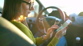 Frau in den Gläsern unter Verwendung eines Smartphone im Auto stock video footage