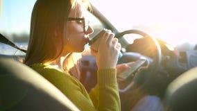 Frau in den Gläsern unter Verwendung eines Smartphone und eines Getränkkaffees im Auto stock video