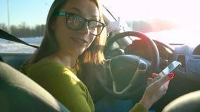 Frau in den Gläsern unter Verwendung eines Smartphone und Unterhaltung mit jemand im Auto stock video