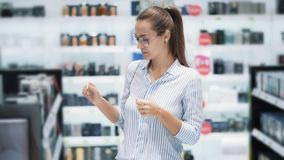 Frau in den Gläsern wählt Parfüm in den Kosmetik kaufen, schnüffeln es, Zeitlupe stock video