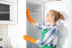 Frau in den Gummihandschuhen, die leeren Kühlschrank säubern stockfotografie