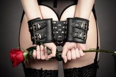 Frau in den Handschellen, die eine Rose halten Lizenzfreies Stockbild
