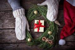 Frau in den Handschuhen, die Weihnachtskranz machen Stockbild