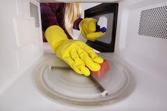 Frau in den Handschuhen mit Schwamm- und Sprühflaschereinigungsmikrowelle Stockfoto