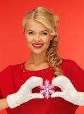 Frau in den Handschuhen und im roten Kleid mit Schneeflocke Stockfoto