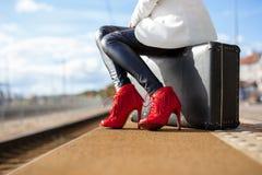 Frau in den hohen Absätzen an der Bahnstation stockfotografie