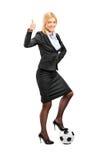 Frau in den hohen Absätzen, die auf einer Kugel stehen Stockfotografie