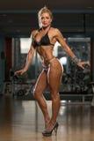 Frau in den hohen Absätzen, die ihren ausgebildeten Körper zeigen Stockfotos