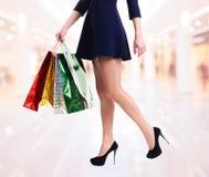 Frau in den hohen Absätzen mit Farbeinkaufstaschen Stockfoto