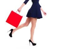 Frau in den hohen Absätzen mit roter Einkaufstasche. Stockbilder