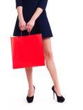 Frau in den hohen Absätzen mit roter Einkaufstasche Stockfoto