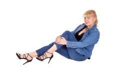 Frau in den Jeans, die auf Boden sitzen Stockfoto