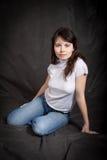 Frau in den Jeans, die auf dem Boden sitzen Stockfotografie
