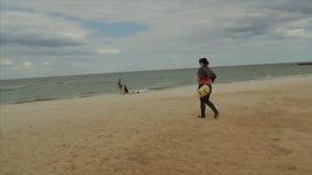Frau in den Jeans tragen Wege entlang dem Strand Geschossen von der Rückseite stock footage