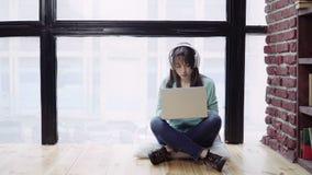 Frau in den Kopfhörern, die an einem Laptop arbeiten stock video